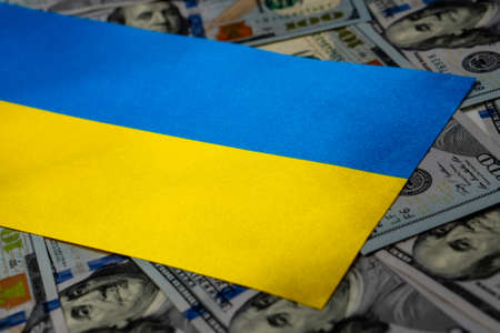 Ukraine flag with US dollars as background. Concept for investors, soft focus