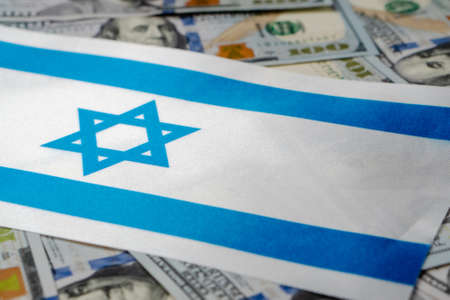 Israel flag with US dollars as background. Concept for investors, soft focus