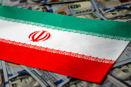Iran flag with US dollars as background. Concept for investors, soft focus