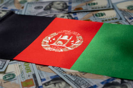 Afghanistan flag with US dollars as background. Concept for investors, soft focus