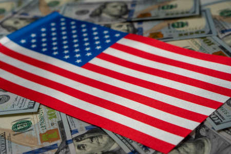 USA Flag with US dollars as background. Concept for investors, soft focus