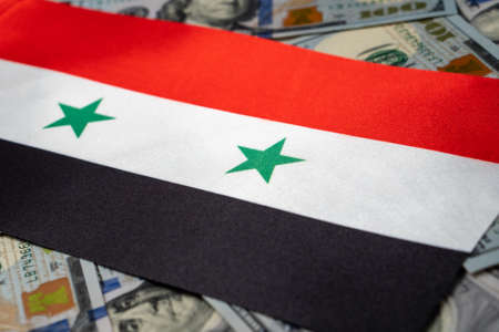 Syria flag with US dollars as background. Concept for investors, soft focus