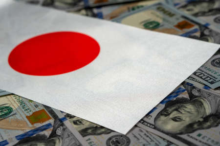 Japan flag with US dollars as background. Concept for investors, soft focus Foto de archivo