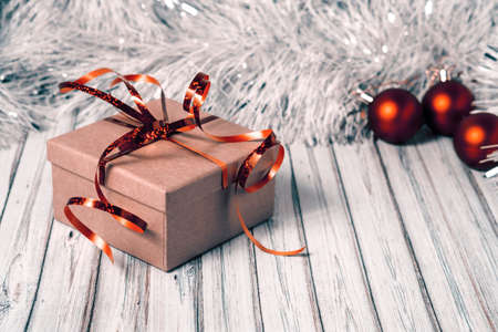 Gift box on a wooden table decorated with a garland and red Christmas balls for the New Year or XMAS. Mail, courier or delivery service concept. Copy space. Foto de archivo