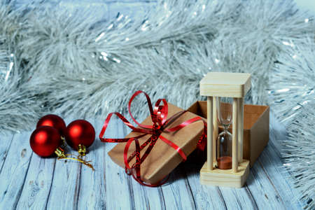 Hourglass and cardboard box on a wooden table decorated with a garland and red Christmas balls for the New Year or XMAS. Mail, courier or delivery service concept. Copy space. Foto de archivo