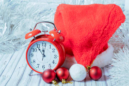 Red vintage alarm clock and Santa hat on a wooden table decorated with a garland and red Christmas balls for the New Year or XMAS. Mail, courier or delivery service concept. Copy space. Foto de archivo
