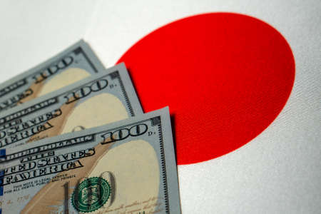 Japan national flag and the dollar bills. Business and finance concept, soft focus Foto de archivo