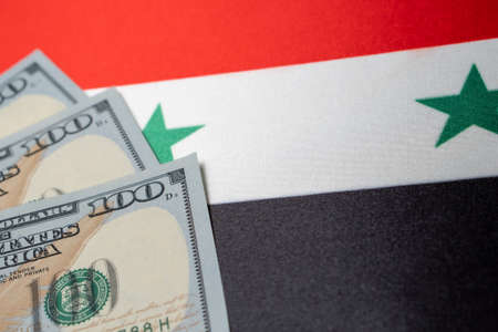 Syria national flag and the dollar bills. Business and finance concept, soft focus