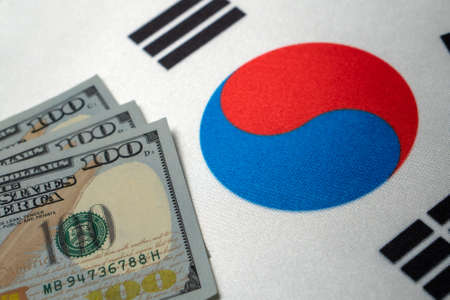 Republic of Korea national flag and the dollar bills. Business and finance concept, soft focus