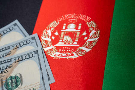 Afghanistan national flag and the dollar bills. Business and finance concept, soft focus