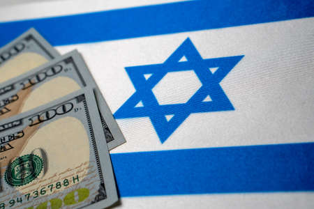 Israel national flag and the dollar bills. Business and finance concept, soft focus