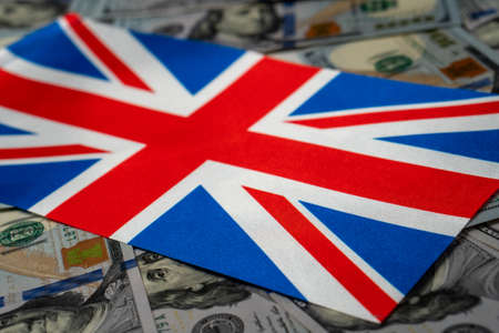 Great Britain flag with US dollars as background. Concept for investors, soft focus