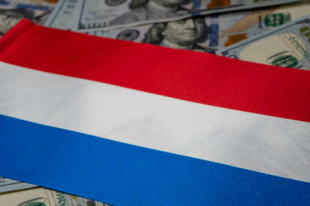 Netherlands flag with US dollars as background. Concept for investors, soft focus Foto de archivo