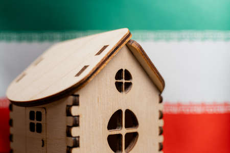 Small wooden house, Iran flag on background. Real estate concept, soft focus.