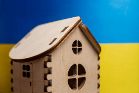 Small wooden house, Ukraine flag on background. Real estate concept, soft focus. Foto de archivo - 152122375