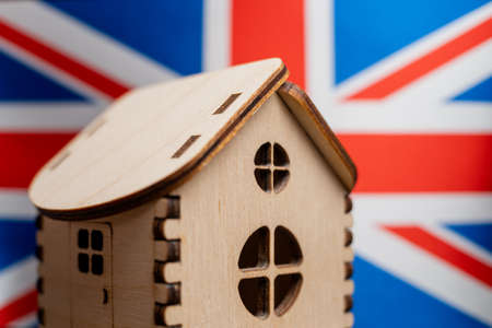 Small wooden house, Great Britain flag on background. Real estate concept, soft focus.