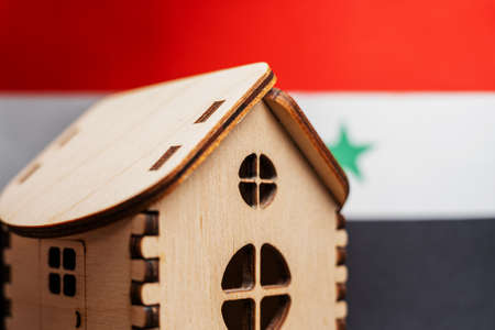 Small wooden house, Iraq flag on background. Real estate concept, soft focus Foto de archivo