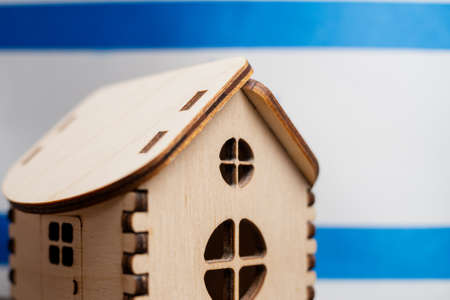 Small wooden house, Israel flag on background. Real estate concept, soft focus.