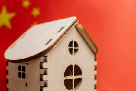 Small wooden house, China flag on background. Real estate concept, soft focus. Foto de archivo