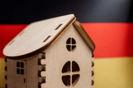 Small wooden house, Germany flag on background. Real estate concept, soft focus. Foto de archivo