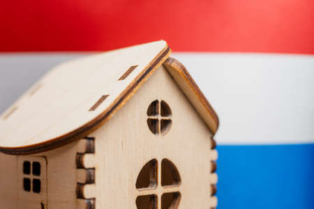 Small wooden house, Netherlands flag on background. Real estate concept, soft focus.