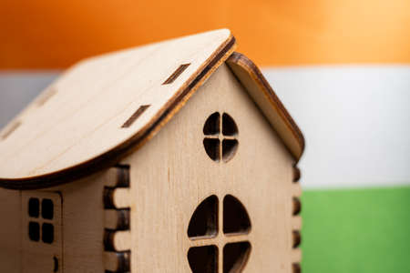 Small wooden house, India flag on background. Real estate concept, soft focus. Foto de archivo - 152122355