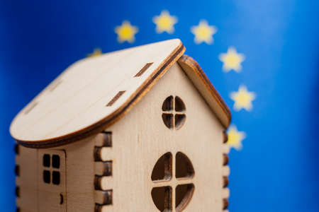 Small wooden house, European Union flag on background. Real estate concept, soft focus. Foto de archivo