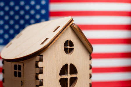 Small wooden house, USA flag on background. Real estate concept, soft focus.