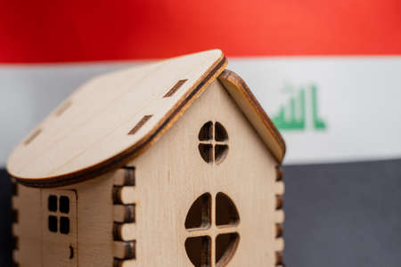Small wooden house, Iraq flag on background. Real estate concept, soft focus. Foto de archivo