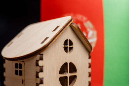 Small wooden house, Afghanistan flag on background. Real estate concept, soft focus. Foto de archivo
