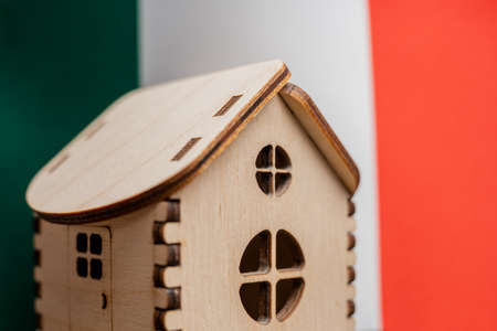 Small wooden house, Italy flag on background. Real estate concept, soft focus. Foto de archivo