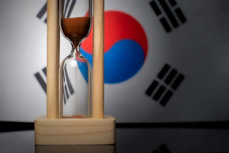 Hourglass and Republic of Korea flag, soft focus, copy space Foto de archivo