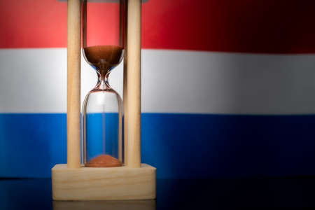 Hourglass and Netherlands flag, soft focus, copy space Foto de archivo