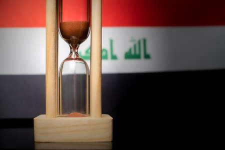 Hourglass and Iraq flag, soft focus, copy space