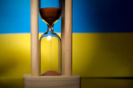 Hourglass and Ukraine flag, soft focus, copy space Foto de archivo