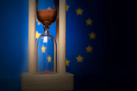 Hourglass and European Union flag, soft focus, copy space