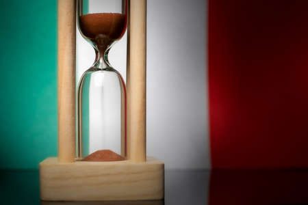 Hourglass and Italy flag, soft focus, copy space