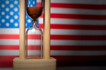 Hourglass and USA flag, soft focus, copy space