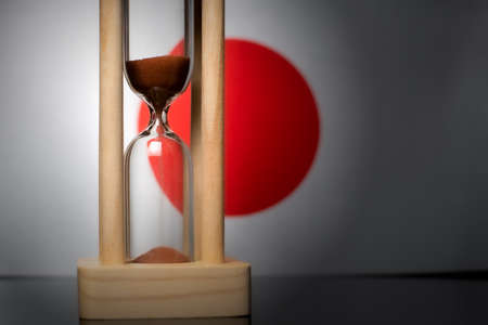 Hourglass and Japan flag, soft focus, copy space