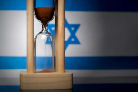 Hourglass and Israel flag, soft focus, copy space