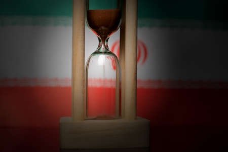 Hourglass and Iran flag, soft focus, copy space