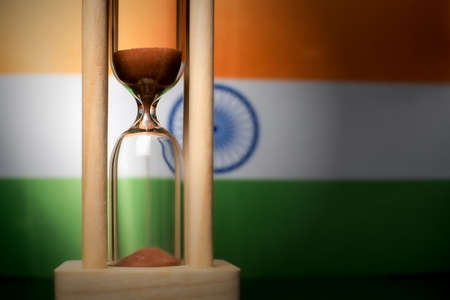 Hourglass and India flag, soft focus, copy space