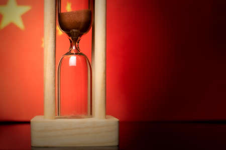 Hourglass and China flag, soft focus, copy space