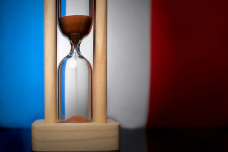 Hourglass and France flag, soft focus, copy space