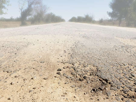 Dangerous road, potholes in the asphalt on the road and fog Banque d'images
