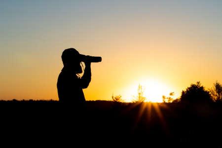 A bearded man looks through binoculars, close-up. The hunter uses binoculars to search. Sunset. Copy spase