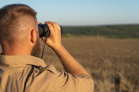 A bearded man looks through binoculars, close-up. The hunter uses binoculars to search