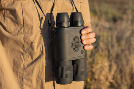 Close up of binoculars in a man's hand