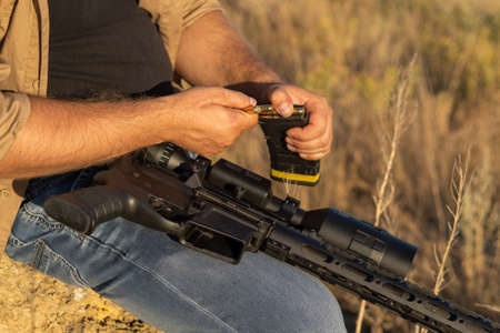 A rifle in a mans hand, close-up. Hunter with a weapon on the hunt against the background of a beautiful summer landscape