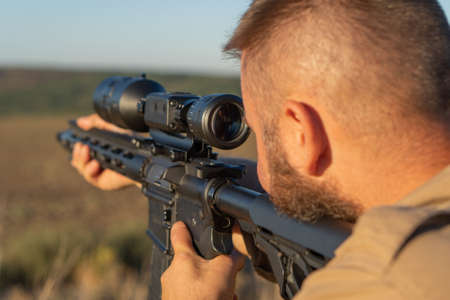 A hunter with a weapon on the hunt against the backdrop of a beautiful summer landscape. Shooter sighting in the target. The Bearded man is on the hunt. Soft focus